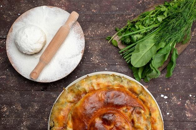 トップビュー調理された緑のペストリーラウンド白いプレートの内側の新鮮な緑と茶色の木製の机の食事食事食品ペストリーグリーン