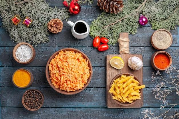 紺色の机の上の調味料で調理された挽き肉の上面パスタ料理の食事皿生地の色