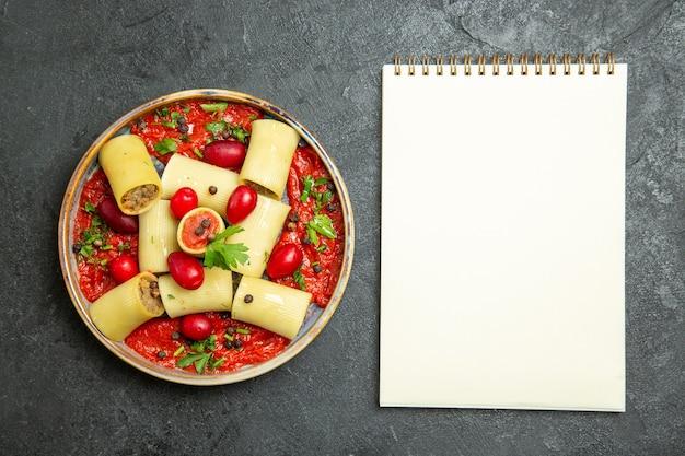 Вид сверху приготовленные итальянские макароны, вкусная еда с мясом и томатным соусом на темно-сером фоне, тесто для пасты, мясной соус, еда