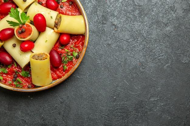 상위 뷰는 회색 책상 파스타 반죽 고기 소스 음식에 고기와 토마토 소스와 함께 이탈리아 파스타 맛있는 식사를 요리