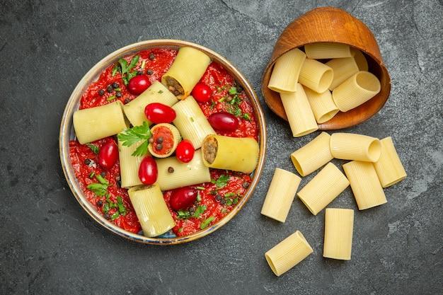 上面図調理済みイタリアンパスタグレーの表面にトマトソースを添えたおいしい食事生地肉フードソースパスタ