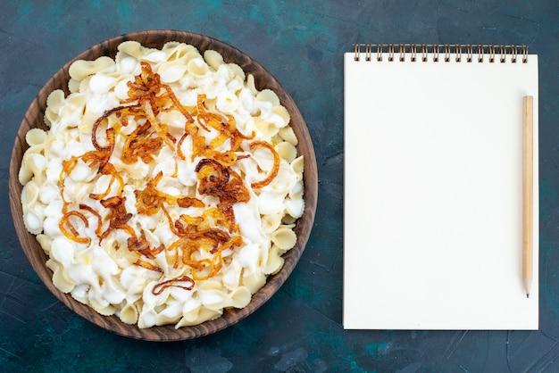 Vista dall'alto cucinato pasta italiana all'interno del piatto sulla scrivania blu