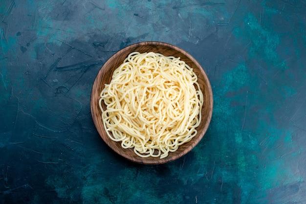 Vista dall'alto di pasta italiana cotta all'interno del piatto di legno rotondo su sfondo blu pasta cibo cena pasta di carne