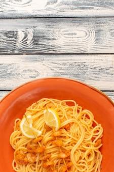 Vista dall'alto di pasta italiana cotta gustosa con fette di limone e gamberetti all'interno del piatto arancione sulla superficie rustica in legno grigio