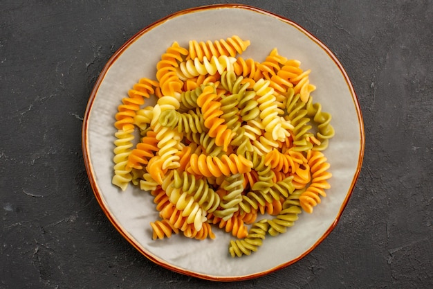 Top view cooked italian pasta unusual spiral pasta inside plate on dark space