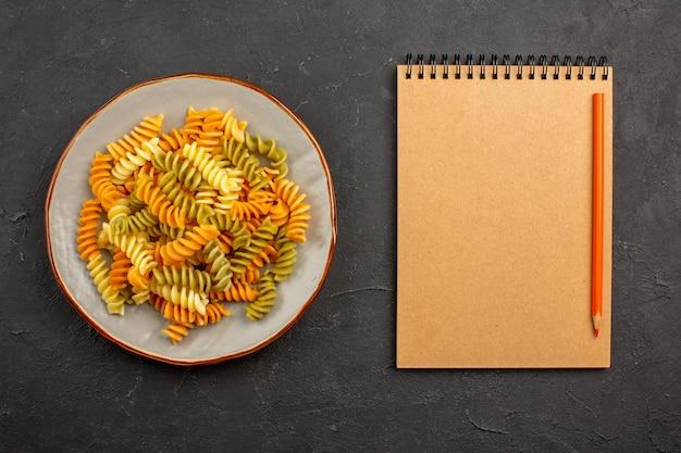 Vista dall'alto pasta italiana cucinata pasta a spirale insolita all'interno del piatto nello spazio buio