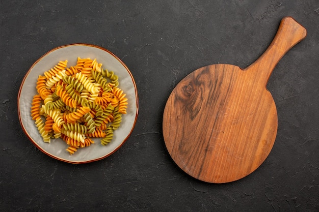Top view cooked italian pasta unusual spiral pasta inside plate on the dark space