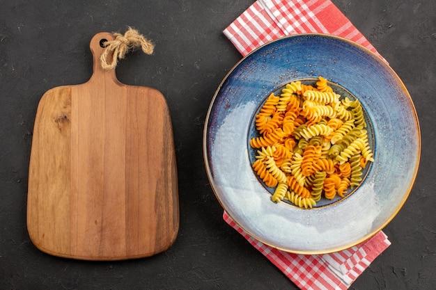 Вид сверху приготовленные итальянские макароны необычные спиральные макароны внутри тарелки на темном пространстве