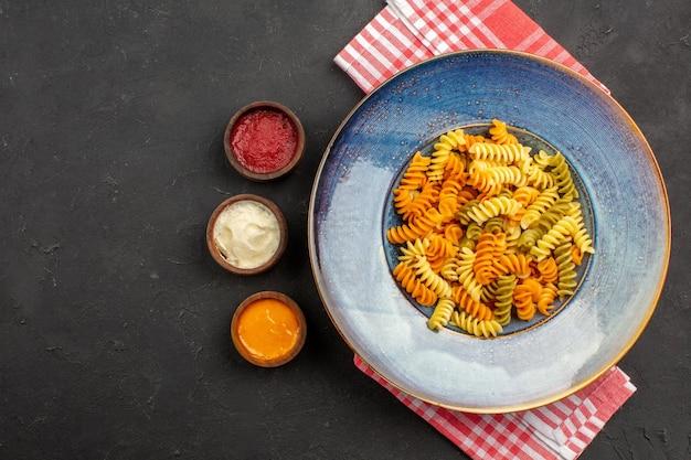 상위 뷰는 어두운 책상 파스타 요리 접시 저녁 식사에 접시 안에 이탈리아 파스타 특이한 나선형 파스타 요리