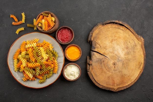 Вид сверху приготовленные итальянские макароны необычные спиральные макароны с приправами на темном пространстве