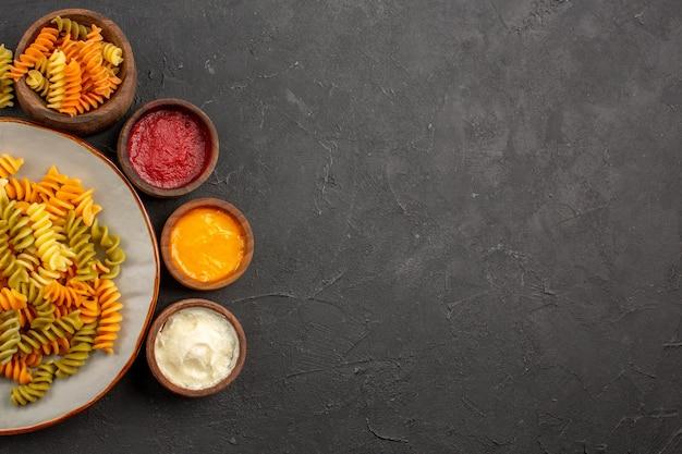 暗い机の上に調味料を入れたイタリアのパスタ珍しいスパイラルパスタのトップビューパスタ料理ディナー料理