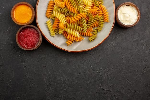 暗い机の上に調味料を入れたイタリアのパスタ珍しいスパイラルパスタのトップビューパスタ食事料理料理ディナー