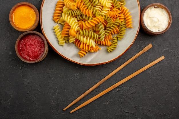暗い床に調味料を入れたイタリアのパスタ珍しいスパイラル パスタのトップ ビュー