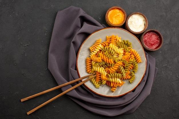 어두운 공간에 조미료와 함께 이탈리아 파스타 특이한 나선형 파스타 요리 상위 뷰