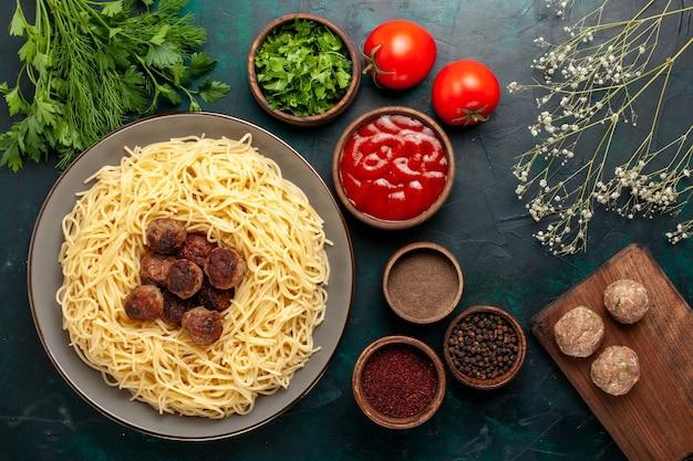Vista dall'alto di pasta italiana cotta con diversi condimenti sulla superficie blu scuro
