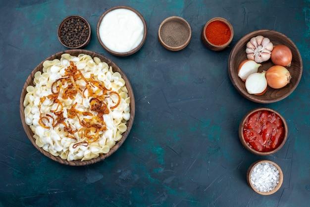 青い机の上にさまざまな調味料で調理されたイタリアンパスタの上面図