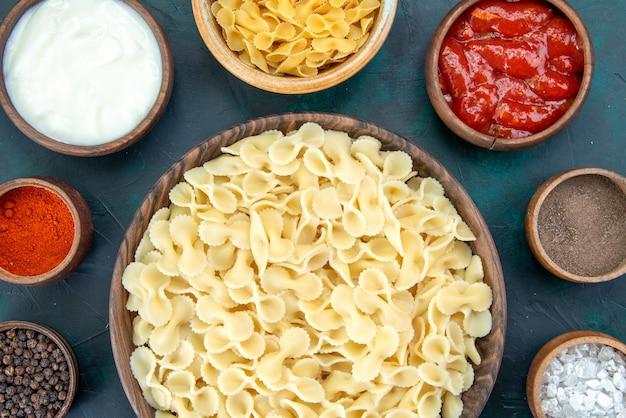 暗い机の上にさまざまな調味料で調理されたイタリアンパスタの上面図