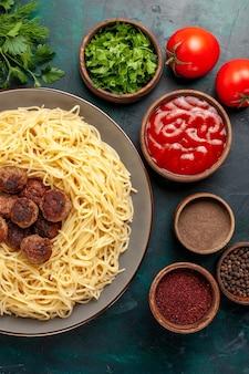 紺色の机の上にさまざまな調味料で調理されたイタリアンパスタの上面図