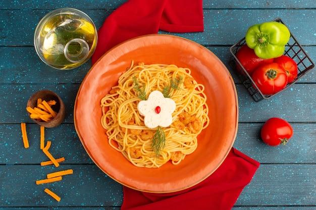 Vista dall'alto di pasta italiana cotta con verdure all'interno del piatto arancione con olio e verdure sulla superficie in legno blu