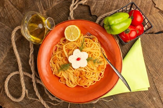 Vista dall'alto di pasta italiana cotta con gamberi verdi e fette di limone insieme a verdure e olio all'interno del piatto arancione