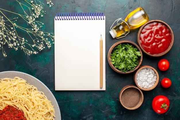 上面図青い表面に肉とさまざまな調味料を使って調理したイタリアンパスタ