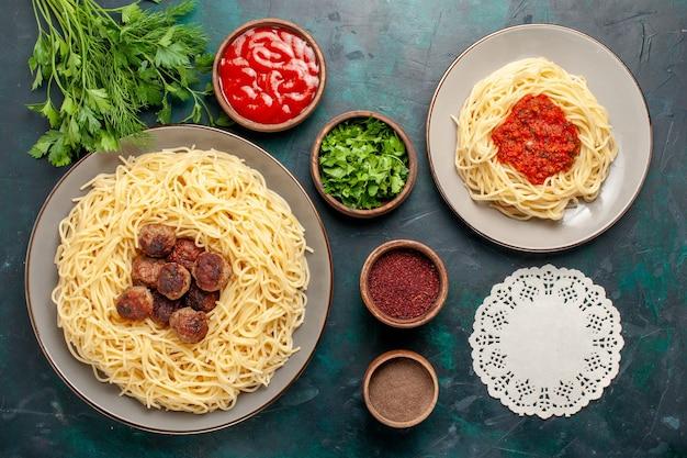 紺色の表面に肉と調味料を添えた上面図調理済みイタリアンパスタ