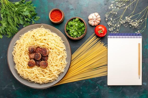 Vista dall'alto cucinato pasta italiana con polpette di carne e verdure sulla superficie blu scuro