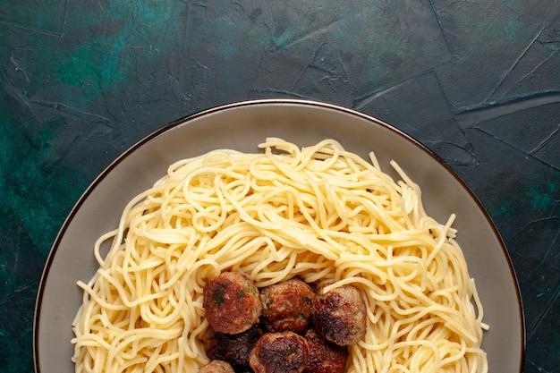 Вид сверху приготовленные итальянские макароны с фрикадельками на темно-синем столе