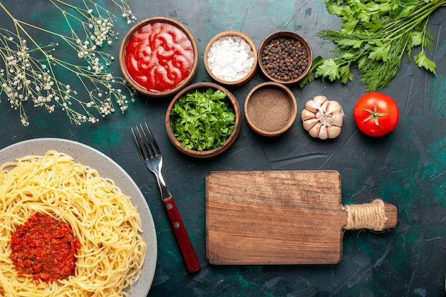 Vista dall'alto di pasta italiana cotta con carne e diversi condimenti sulla superficie blu