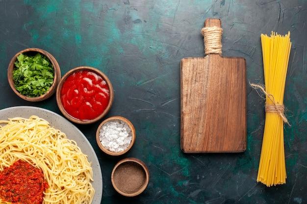 Vista dall'alto cotta pasta italiana con carne e diversi condimenti sulla superficie blu scuro