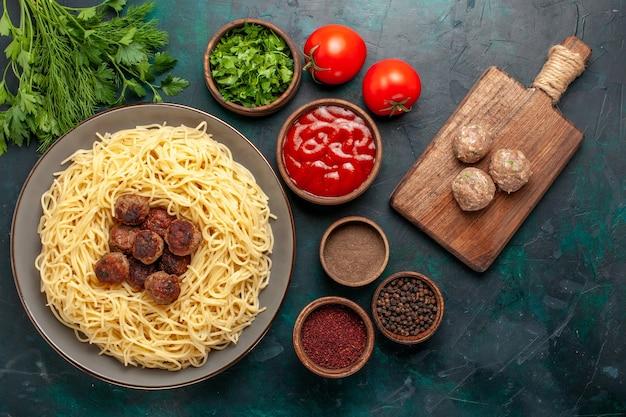 Vista dall'alto cotta pasta italiana con polpette di carne e diversi condimenti sulla superficie blu