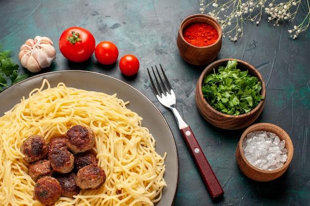 紺色の表面にミートボールの調味料と野菜を添えた上面図調理済みイタリアンパスタ