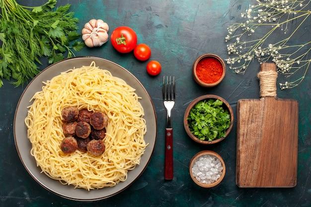 Vista dall'alto cucinato pasta italiana con condimenti di polpette e verdure sulla scrivania blu scuro