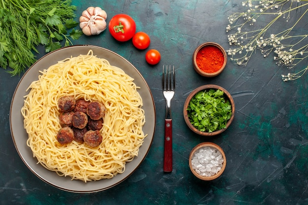 Top view cooked italian pasta with meatballs seasonings and greens on the dark-blue surface