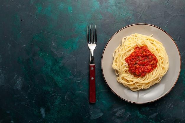 Вид сверху приготовленные итальянские макароны с фаршем и томатным соусом на темно-синей поверхности