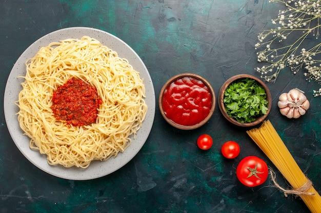 Вид сверху приготовленные итальянские макароны с томатным соусом из фарша и приправами на синей поверхности