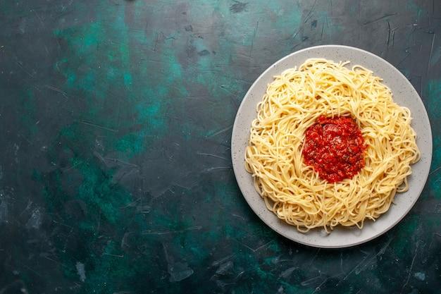 Vista dall'alto cucinato pasta italiana con carne macinata e salsa di pomodoro sulla scrivania blu scuro