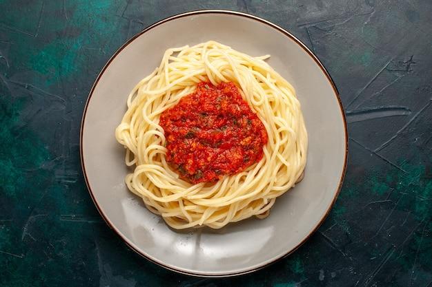 Vista dall'alto cucinato pasta italiana con carne macinata e salsa di pomodoro sulla superficie blu scuro