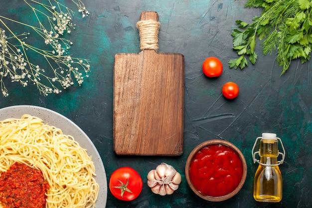 紺色の机の上にトマトのひき肉と油で調理されたイタリアンパスタの上面図