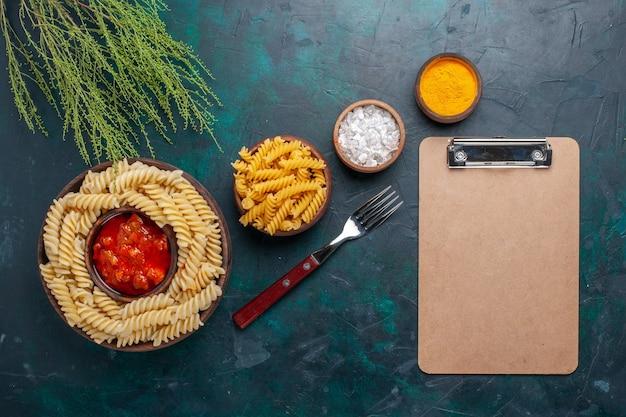 暗い表面にメモ帳ソースと調味料を添えた上面図調理済みイタリアンパスタ