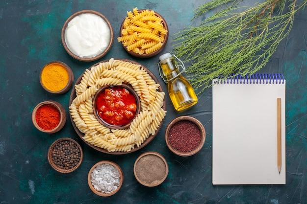Вид сверху приготовленной итальянской пасты с соусом и приправами на темной поверхности