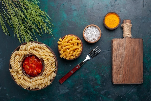 Top view cooked italian pasta with sauce and different seasonings on dark surface