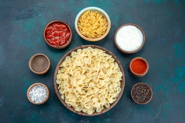 Vista dall'alto di pasta italiana cotta con condimenti su oscurità