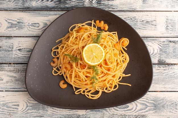 Vista dall'alto di pasta italiana cotta con gamberi verdi e limone all'interno del piatto marrone sulla superficie di legno grigia
