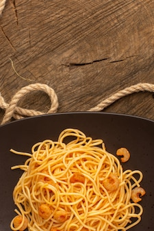 Top view of cooked italian pasta with shrimps inside brown plate with ropes on the wooden desk