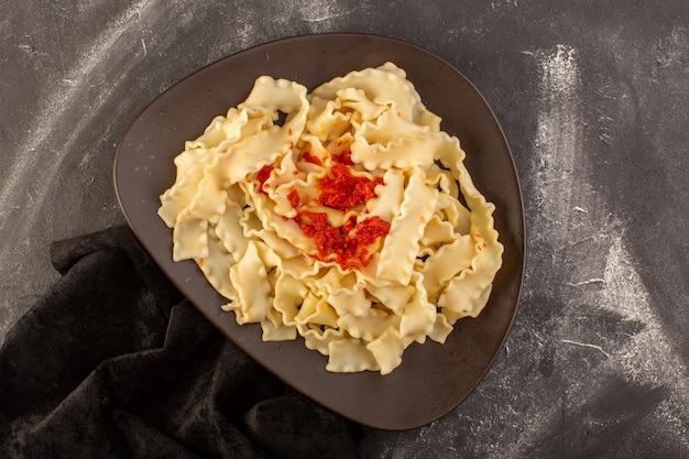Una vista superiore ha cucinato la pasta italiana con salsa di pomodoro all'interno del piatto sulla pasta italiana del pasto dell'alimento della tavola grigia