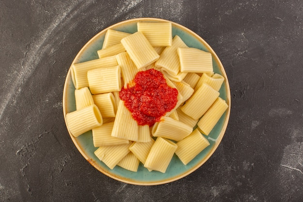 A top view cooked italian pasta with tomato sauce inside plate