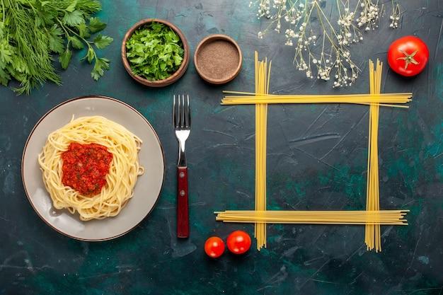 Вид сверху приготовленные итальянские макароны с мясным фаршем в томатном соусе и разными приправами на синей поверхности