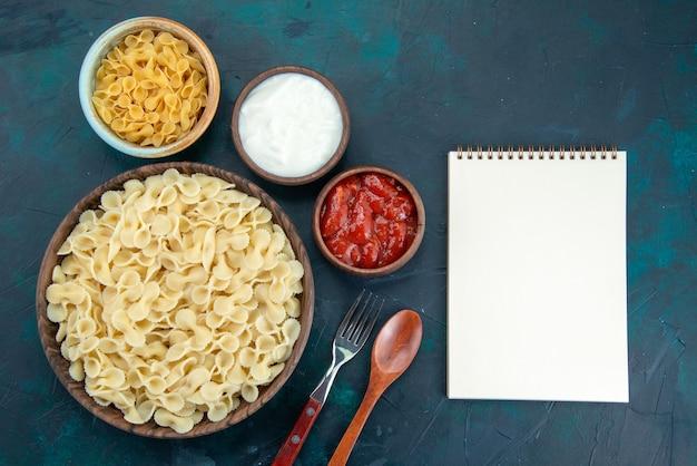 上面図青い机の上にトマトソースで調理されたイタリアンパスタ