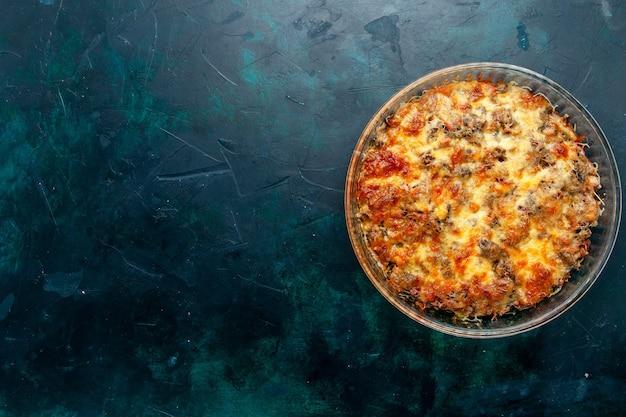 Вид сверху приготовленная мясная еда с овощами и нарезанным мясом вместе с сыром на темно-синем фоне еда блюдо из мясной еды ужин в духовке